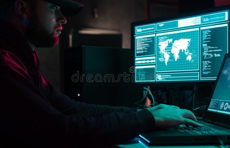 Hacker ricercati che codificano virus Ransomware utilizzando computer e laptop nello scantinato Attacco cibernetico, rottura del  immagine stock libera da diritti