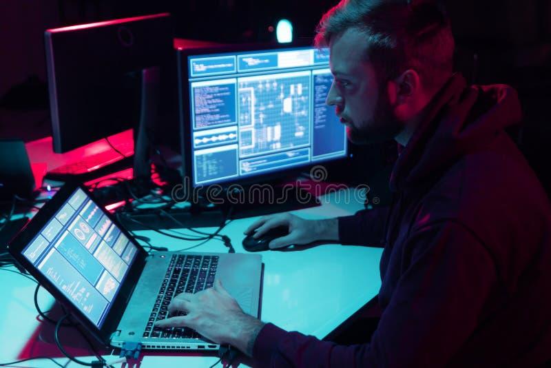 Hacker ricercati che codificano virus Ransomware utilizzando computer e laptop nello scantinato Attacco cibernetico, rottura del  immagine stock