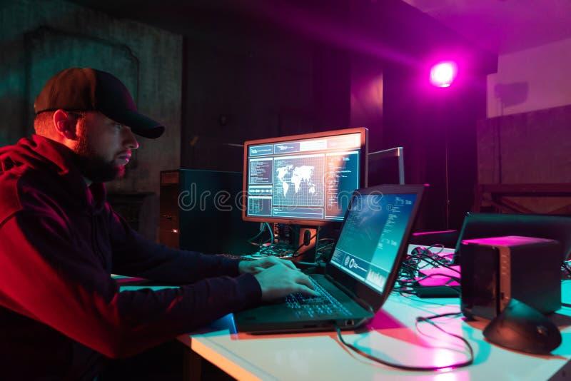 Hacker ricercati che codificano virus Ransomware utilizzando computer e laptop nello scantinato Attacco cibernetico, rottura del  immagini stock libere da diritti