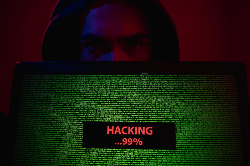 Hacker showing laptop with attack process. Man in hoodie demonstrating modern laptop with hacking process on screen under red illumination royalty free stock photos