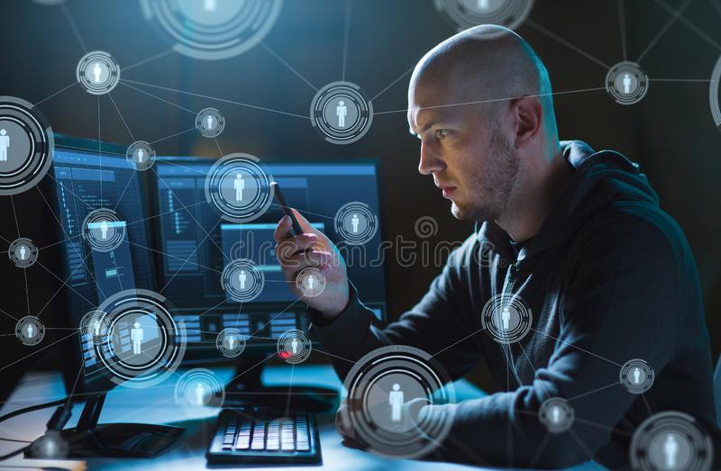Hacker with smartphone and computers in dark room. Cybercrime, hacking and technology concept - male hacker with smartphone and computers networking in dark room royalty free stock photos