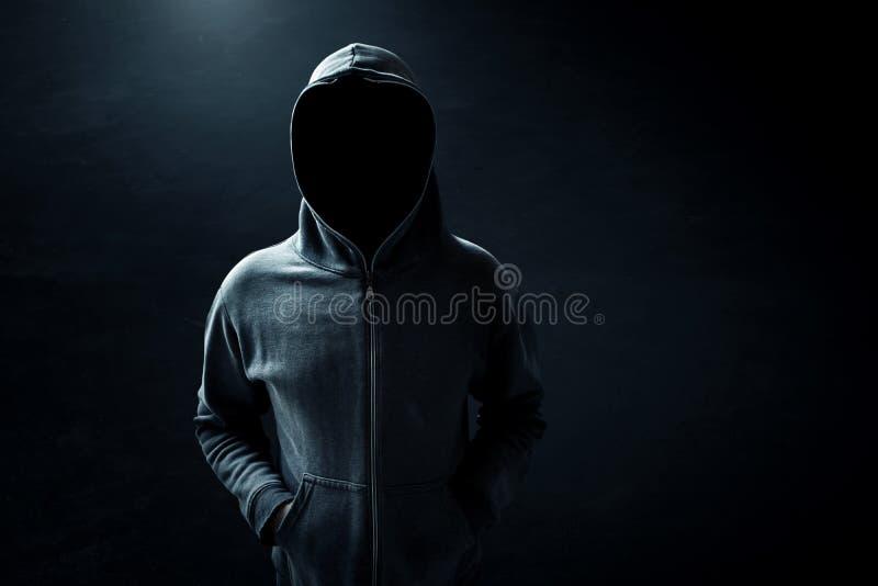 Hacker standing alone. In dark room stock photography