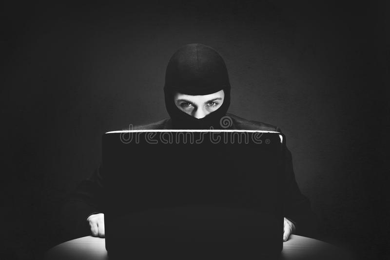 Hacker stealing computer data at night. Hacker wearing a mask or balaclava stealing computer data at night from a compromised laptop computer in a conceptual stock image