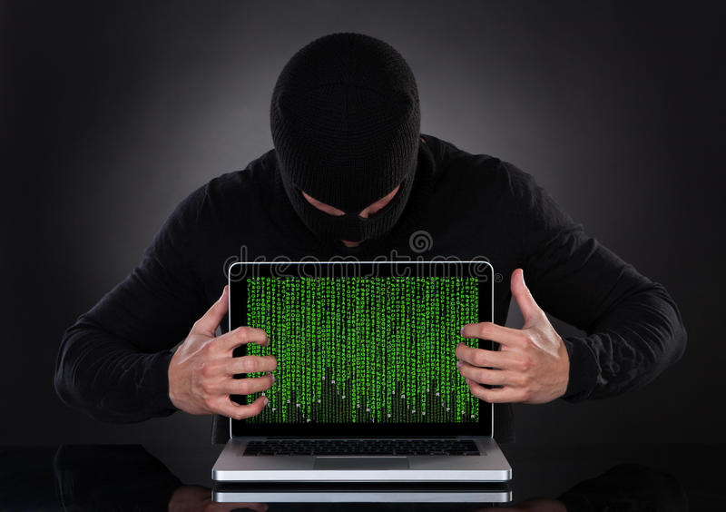 Hacker stealing data of a laptop computer. Hacker in a balaclava standing in the darkness furtively stealing data royalty free stock photo
