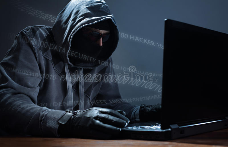Hacker stealing data from a laptop stock photos