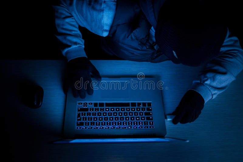 Hacker thief with laptop royalty free stock images