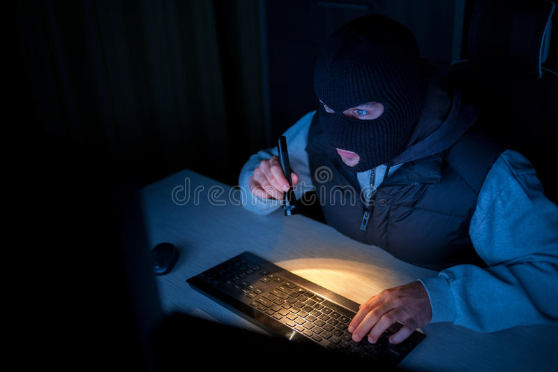 Hacker thief. Typing on keyboard stock image