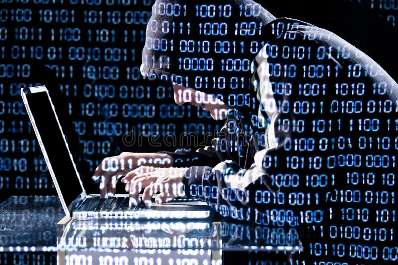 Hacker typing on a laptop. With binary code in background royalty free stock image