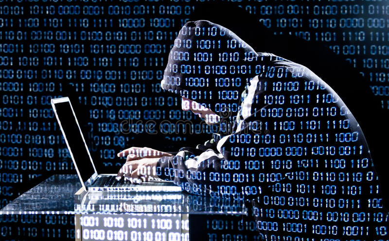 Hacker typing on a laptop. With binary code in background stock images