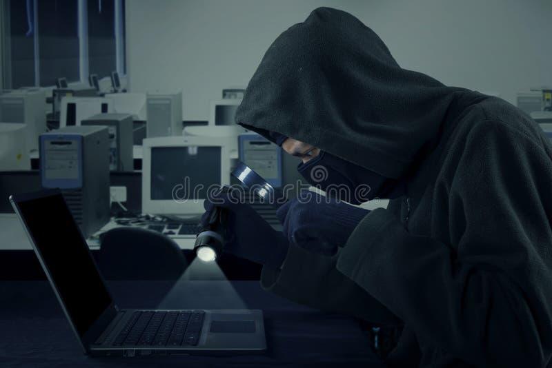 Hacker używa latarkę i powiększający - szkło zdjęcia stock