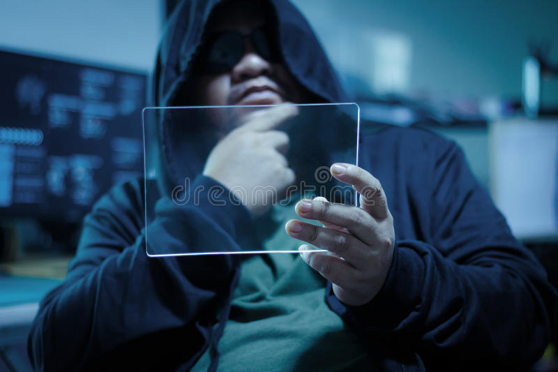 Hacker using blank clear glass tablet with dark and grain process concept for cyber technology data and network hacking criminal stock image