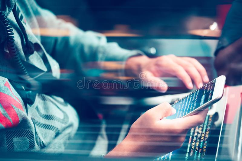 Hacker using computer, smartphone and coding to steal password a. Nd private data remotely from car. Screen displaying program code, website development stock image