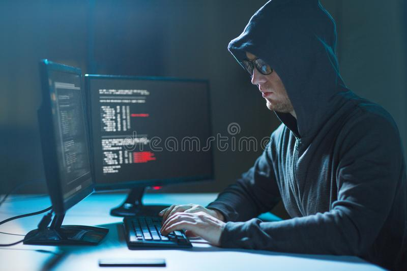 Hacker using computer virus for cyber attack. Cybercrime, hacking and technology concept - male hacker in dark room writing code or using computer virus program royalty free stock photography