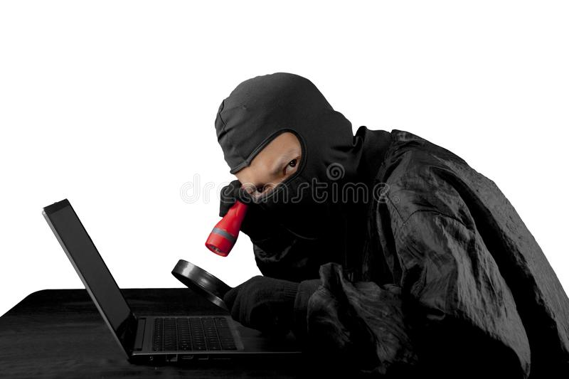 Hacker using flash light and magnifying glass. royalty free stock image