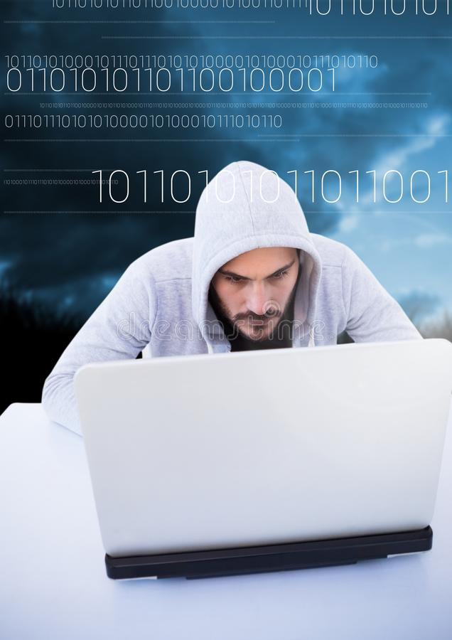 Hacker using a laptop in front of blue background with digital numbers royalty free stock photo