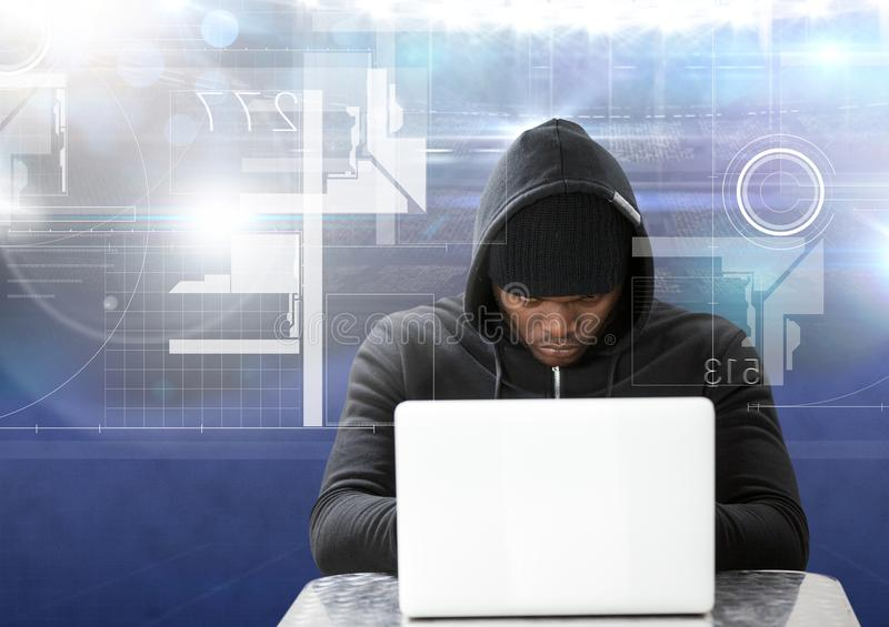Hacker using a laptop in front of blue digital background royalty free stock photo