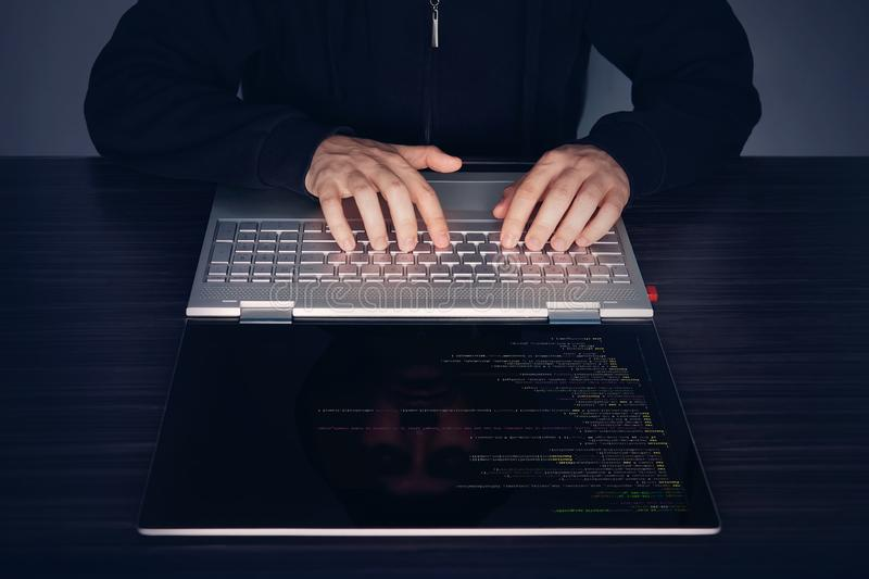 Hacker using laptop. Lots of digits on the computer screen. modern slim ultrabook transformer on the table. program code amer, sof. Tware code, programme code royalty free stock photos