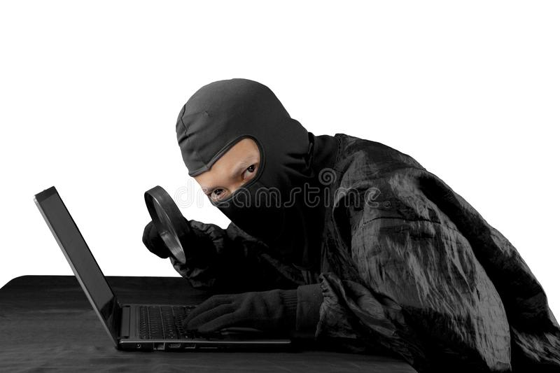 Hacker using magnifying glass on a laptop computer stock photography