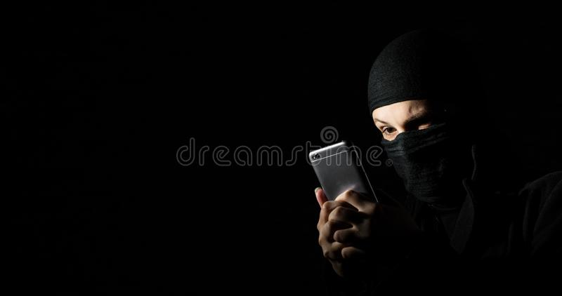 Hacker Using Smart Phone. Young adult girl in black clothes with hidden face looks at smartphone screen on black background with c royalty free stock image