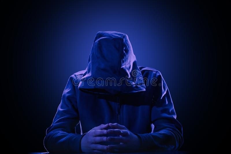 Hacker, violation of intellectual property rights concept. Hacker in a hood on black background. The violation of intellectual property rights concept royalty free stock image