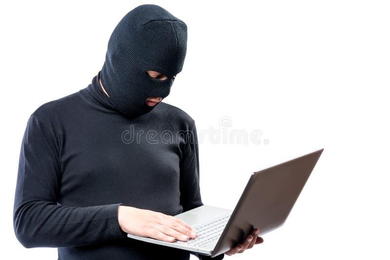 Hacker w czerni ubraniach i maska z laptopem na bielu zdjęcia stock