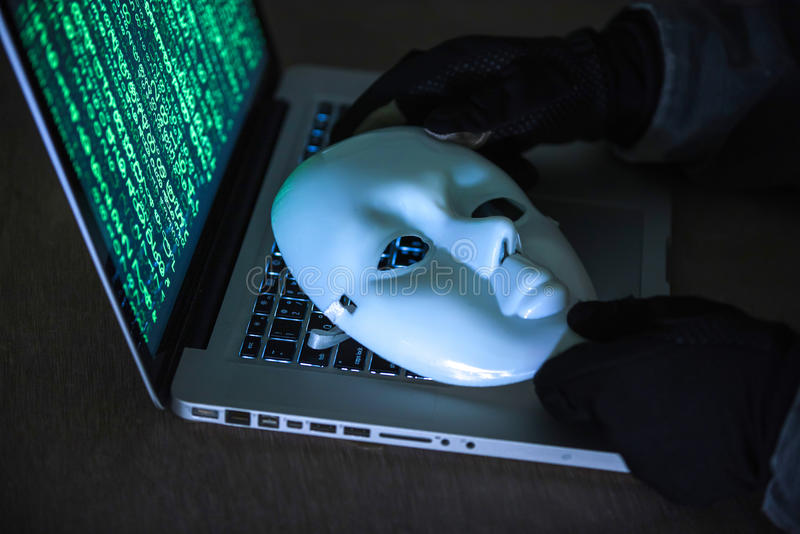 Hacker wear an anonymous mask. Hacker in a mask.Terrorist working on his computer. Concept about terrorist and bandit royalty free stock images