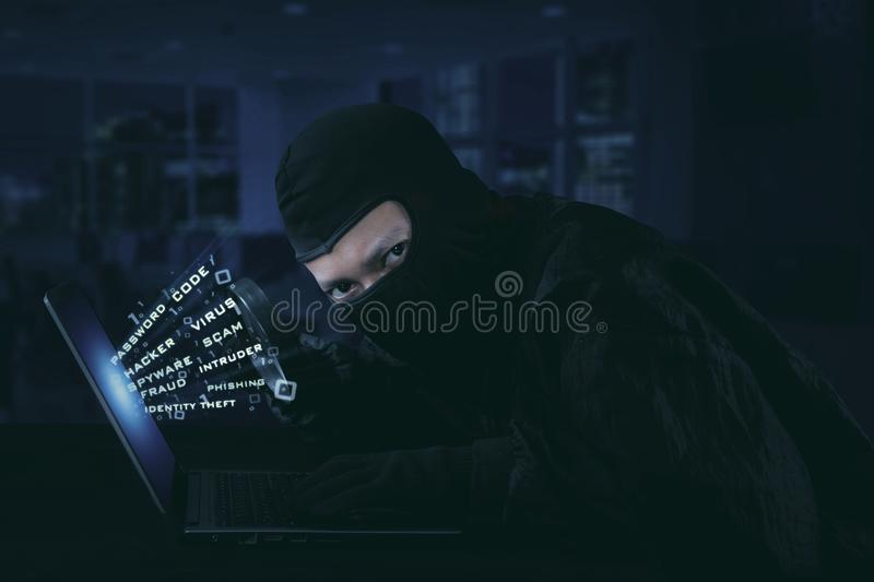 Hacker wearing mask using flash light. Internet security concept stock photos
