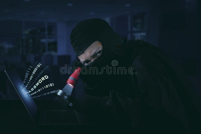 Hacker wearing mask using flash light. Internet security concept stock image