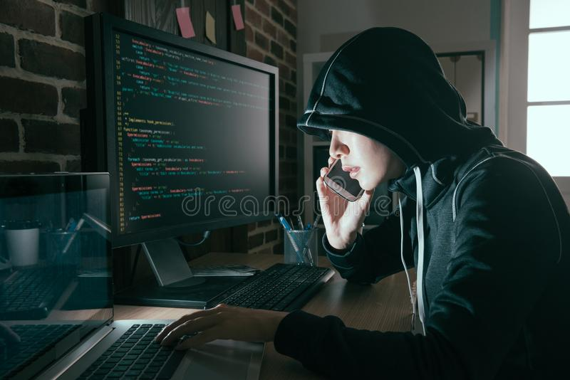 Hacker woman hidden face using mobile cell phone royalty free stock photo