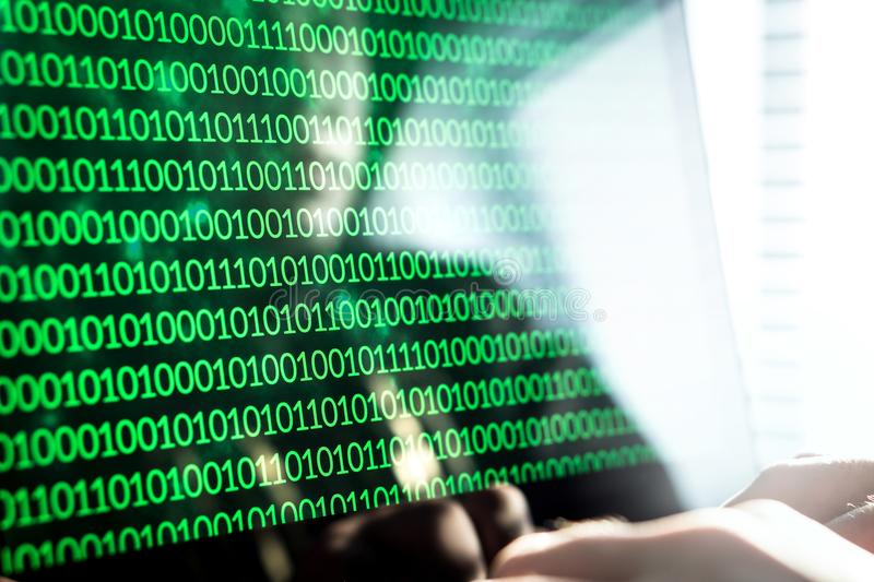 Hacker writing code with laptop computer. Binary numbers, zero and one on monitor screen. Cyber security threat, attack and online crime concept royalty free stock photo