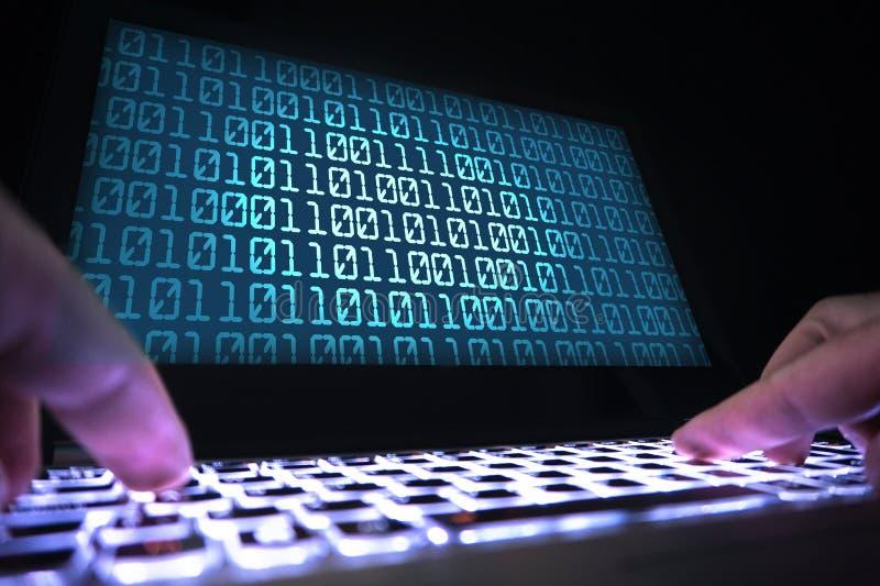 Hackera writing wirusowy kod z laptopem w zmroku zdjęcia stock