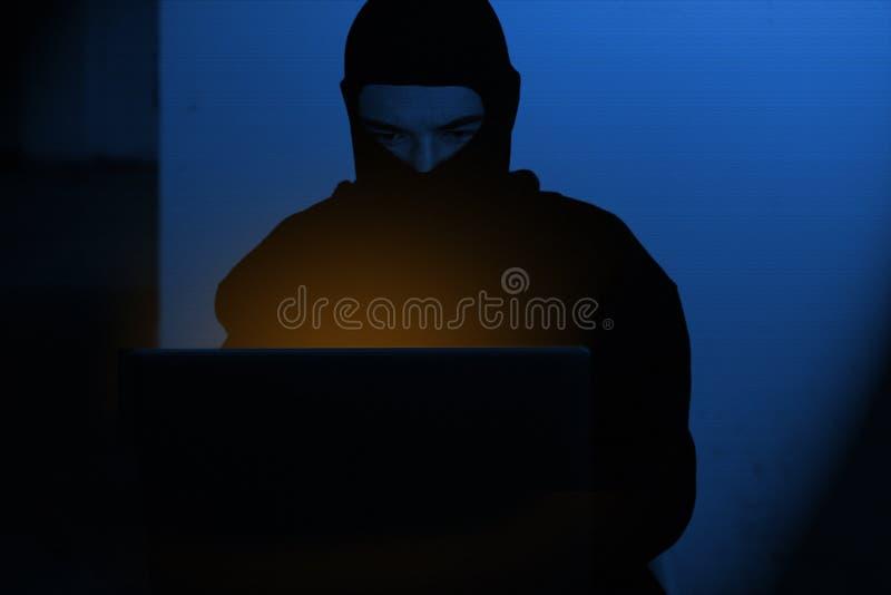 Hackermann im Hoodiehemd schreibend, globale netwok Sicherheit zerhackend lizenzfreies stockbild