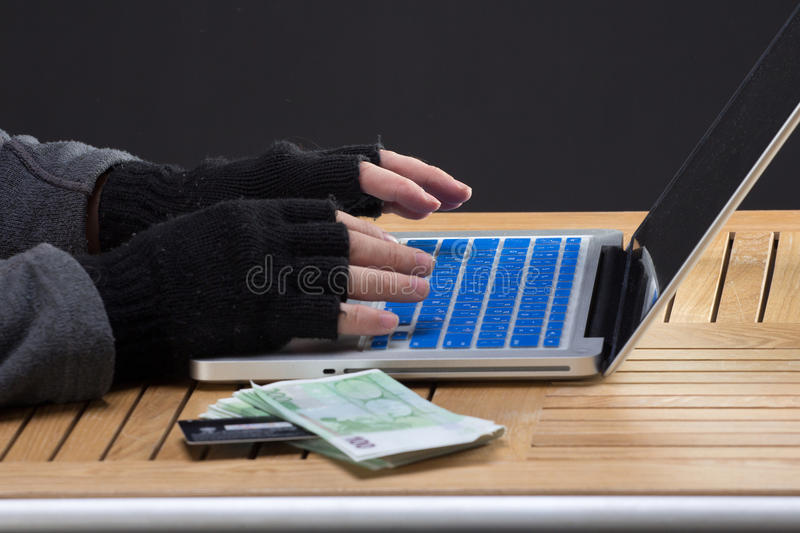 Hackers hands on keybord. With stolen money and credit card royalty free stock photo
