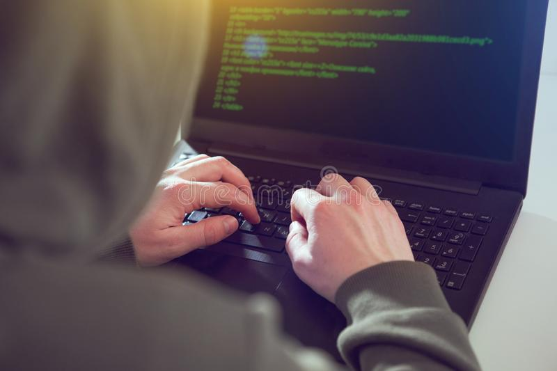 Hackers programmer look on screen and writes the program code hack information and user account stock images
