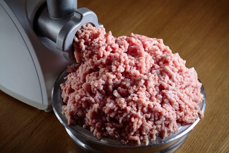 Hackfleisch, das vom modernen elektrischen Schleifer auf eichenem Tisch herauskommt stockbilder