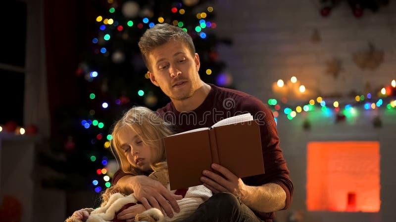 Hada-cuento atento de la Navidad de la lectura del papá para la muchacha soñolienta cerca del árbol adornado imagenes de archivo