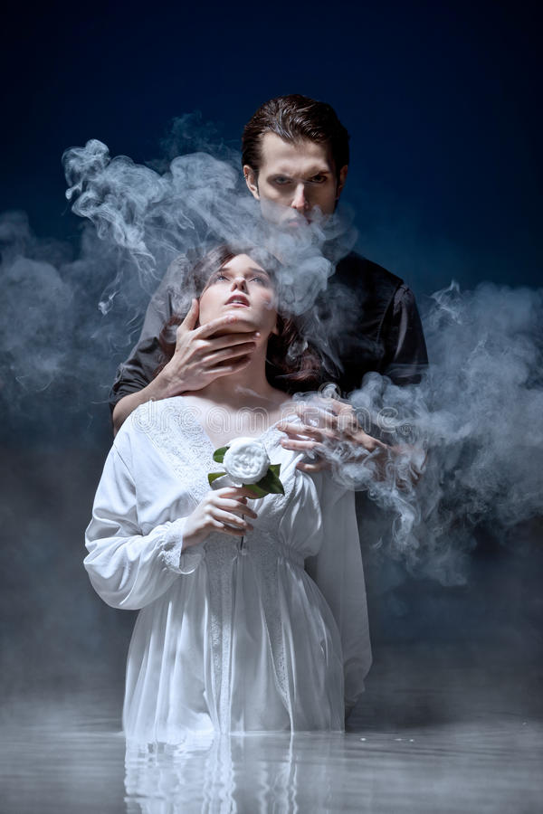 Hades & Persephone: The Seduction. Dark-haired, sinister, masterful men dressed all in black standing behind youthful virginal girl in pure white dress holding a