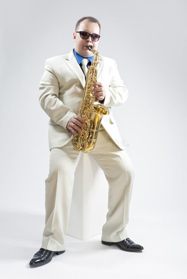 Hadnsome男性萨克管演奏员画象执行在演播室环境的 佩带的白色衣服和太阳镜 库存图片