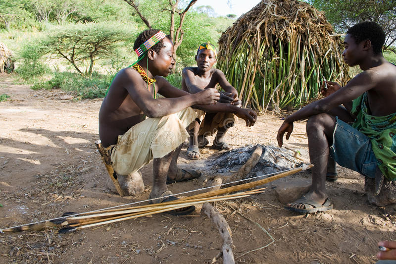 Hadzabe Bushmen. LAKE EYASI, TANZANIA - FEBRUARY 18: A unidentified group of men from Hadza tribe sit around the fire in front of the hut, on February 18, 2013 stock photo
