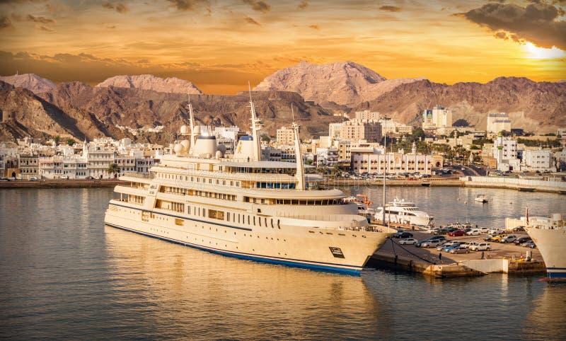 Hafen von Muscat in Oman mit Schiffen bei Sonnenuntergang stockfotos