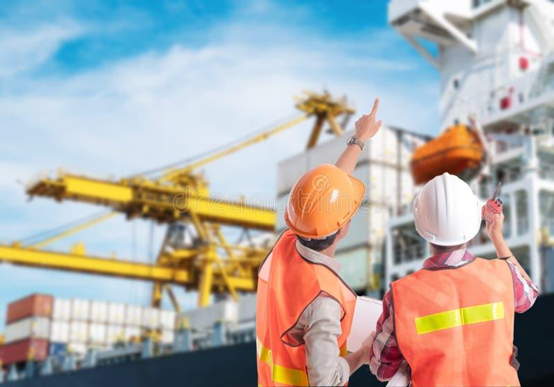 Hafenarbeiter, der Finger auf Steuerung des Behälterladens zeigt lizenzfreies stockfoto