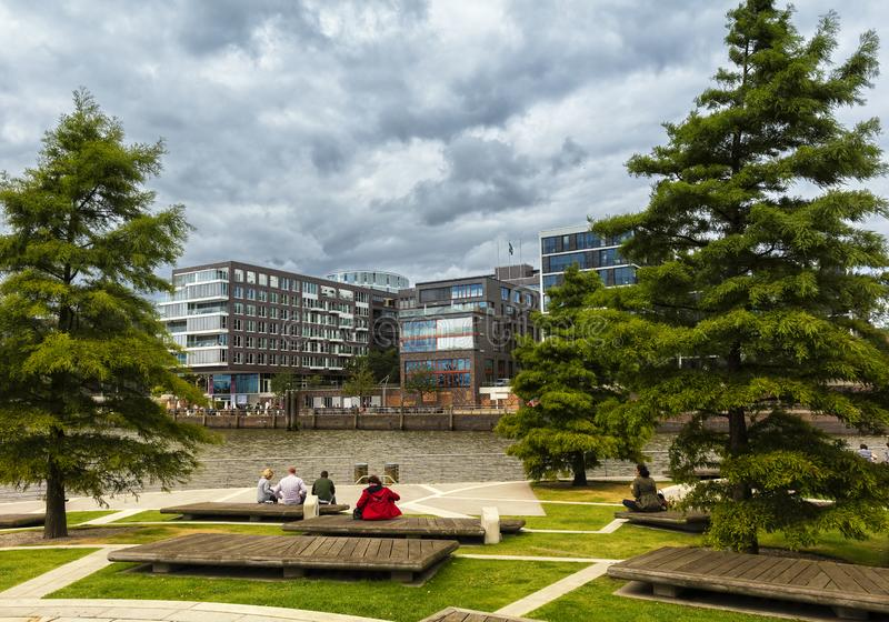 Tourists sit on a bench and look in the direction of the newly built Hafencity in Hamburg stock photo