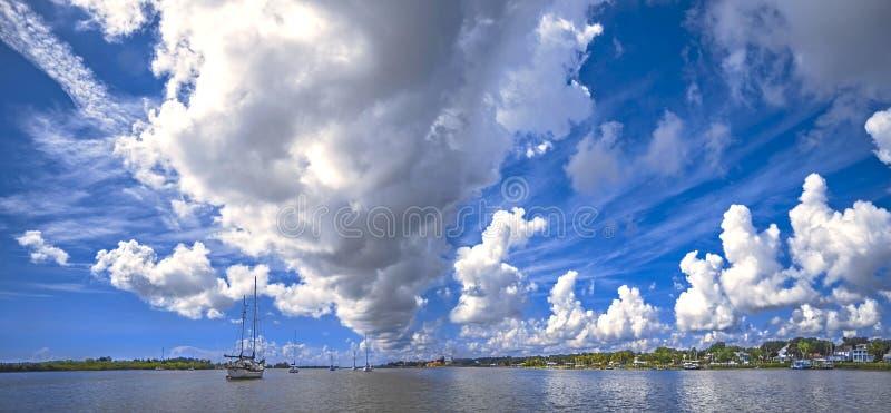 Hafenpanorama mit Dorf auf Ufer und Yachten und Boote auf Wasser lizenzfreie stockbilder