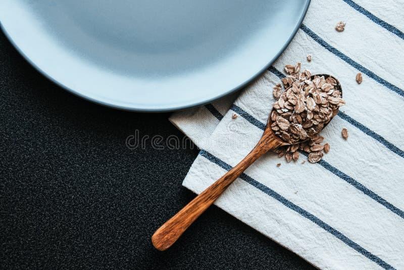 Hafer in einer grauen Platte und einem Geschirrtuch des hölzernen Löffels Bestandteile zum gesundes Fr?hst?ck lizenzfreies stockfoto