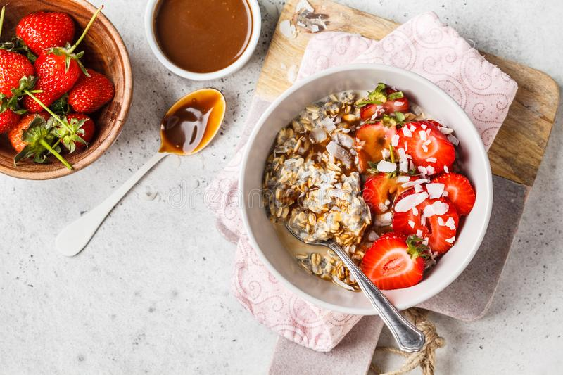 Hafermehl Frühstück des strengen Vegetariers mit chia Samen, Beeren, Samen und Karamell in der weißen Schüssel, Kopienraum lizenzfreies stockbild