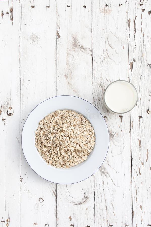 Hafermehl, Haferflocken auf einer Platte mit Glas Milch auf weißem Holz stockbilder