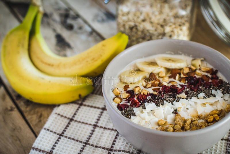 Hafermehl mit Bananen, Moosbeere, chia Samen, Kokosnussfetzen, alm stockbild
