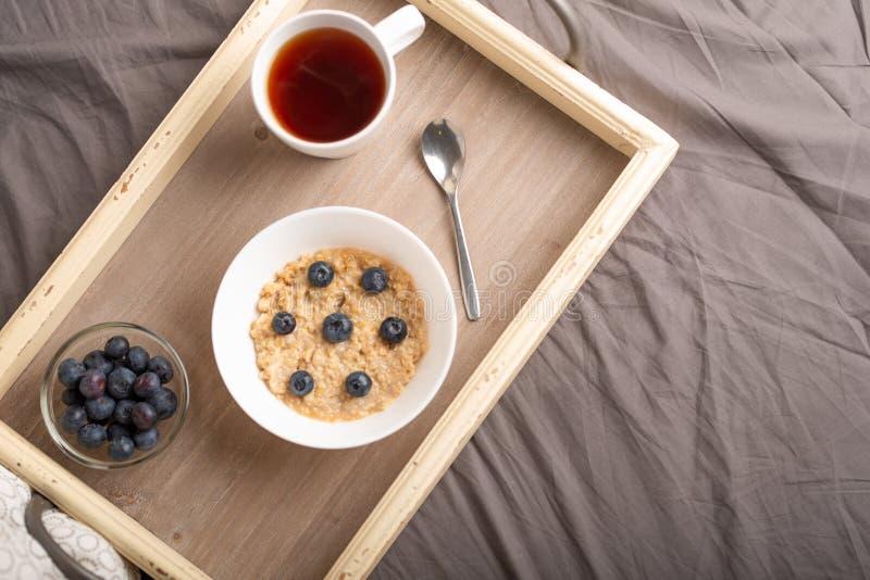 Hafermehl mit Beeren auf einem Beh?lter im Bett mit Tee, Morgenfr?hst?ck und Stimmung Flache Lage gut und warm stockfotos