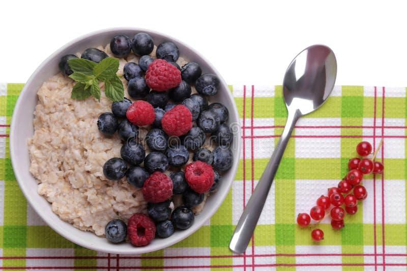 Hafermehl mit Beeren auf Weiß lokalisiertem Hintergrund Gesundes Lebensmittel des Frühstücks lizenzfreies stockfoto