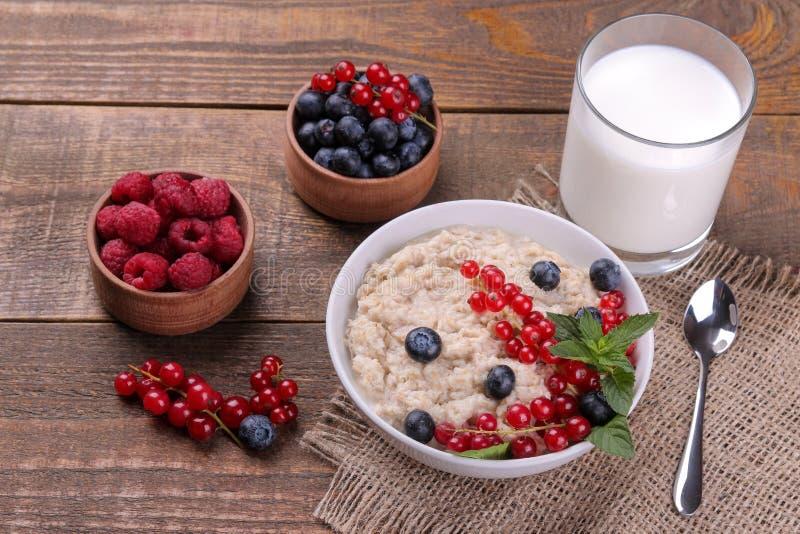 Hafermehl mit Beeren und Milch auf einem braunen Holztisch Gesundes Lebensmittel des Frühstücks lizenzfreies stockbild